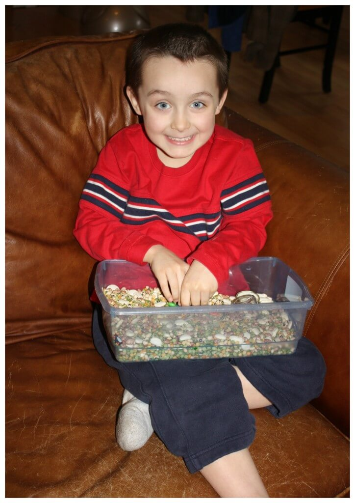 calming sensory bin sitting on couch smiling