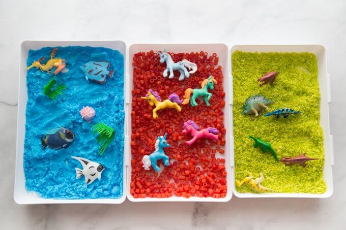 sensory bins made with colored rice, pasta, and salt