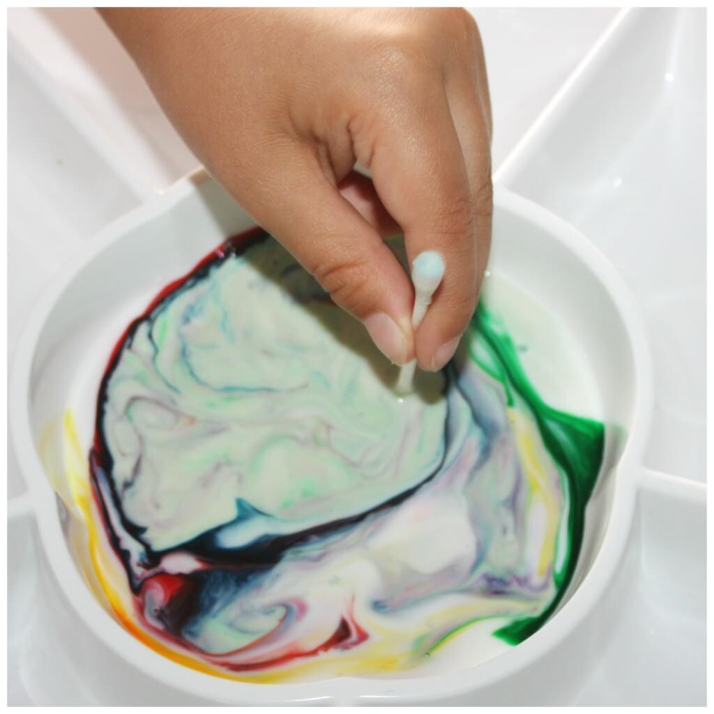 magic milk dipping soapy q tip in milk