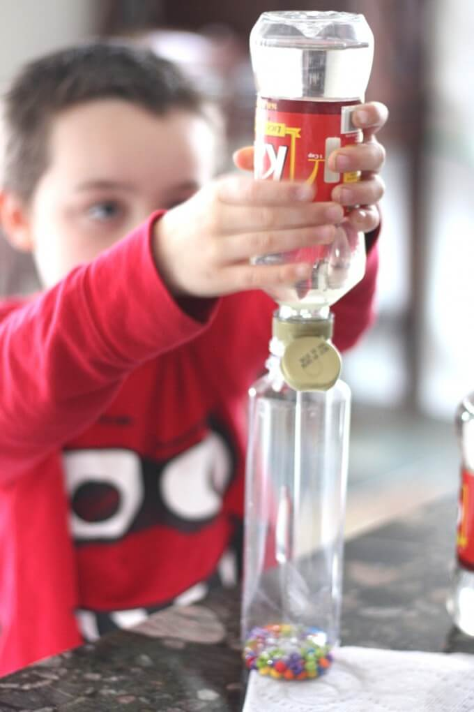 Making LEGO discovery bottles with kids squeezing corn syrup