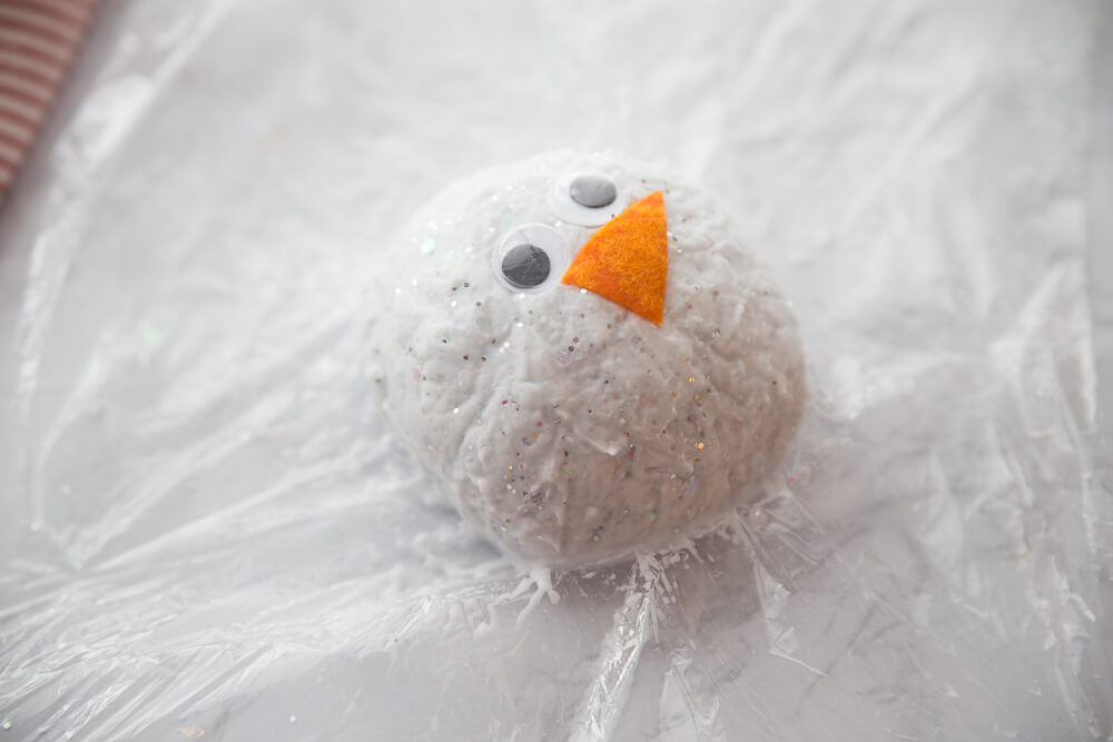fizzing snowball snowman for winter science, use plastic wrap to help form snowball