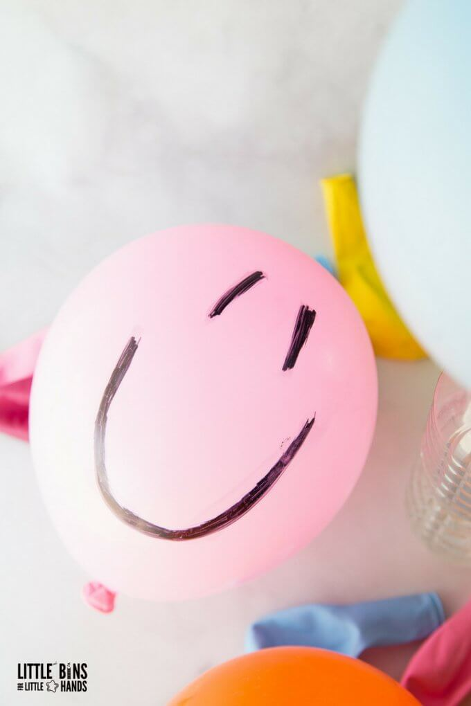 Balloon baking soda science with happy face drawn on pink balloon