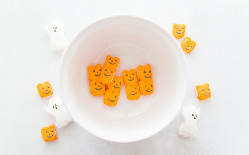 Adding Peeps pumpkins to a bowl for our Peeps Halloween slime recipe