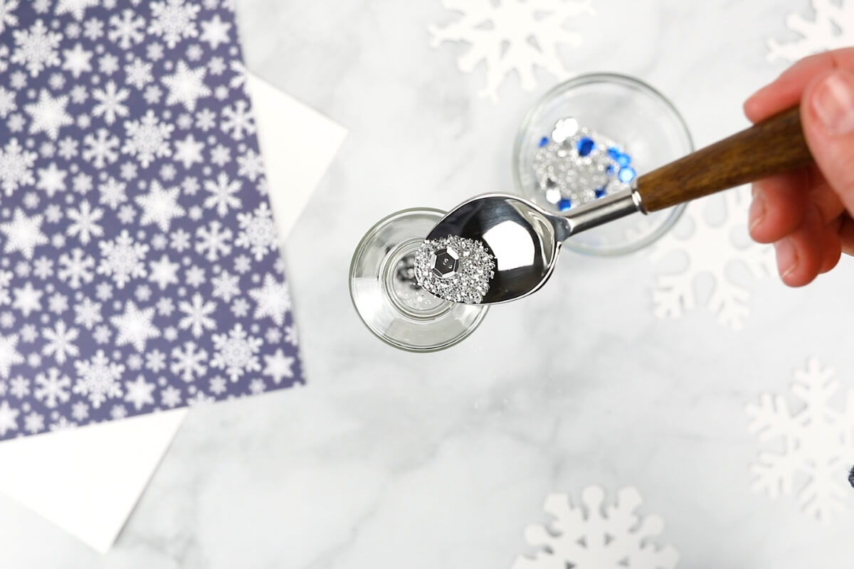Adding glitter to snowman sensory bottle