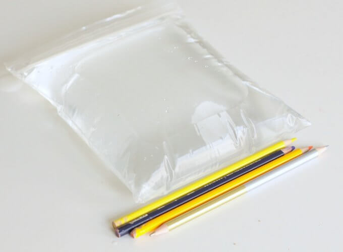 sharpened pencils and bag filled with water on table