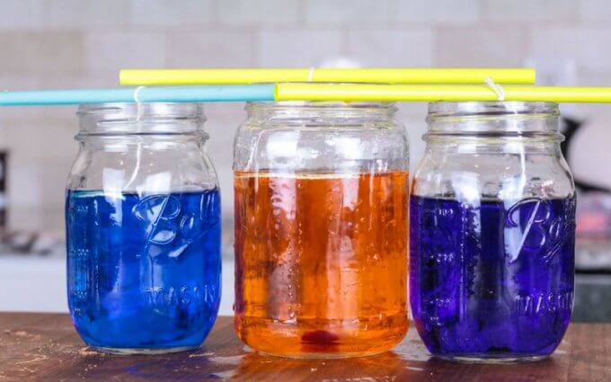colored sugar water with strings in them on counter