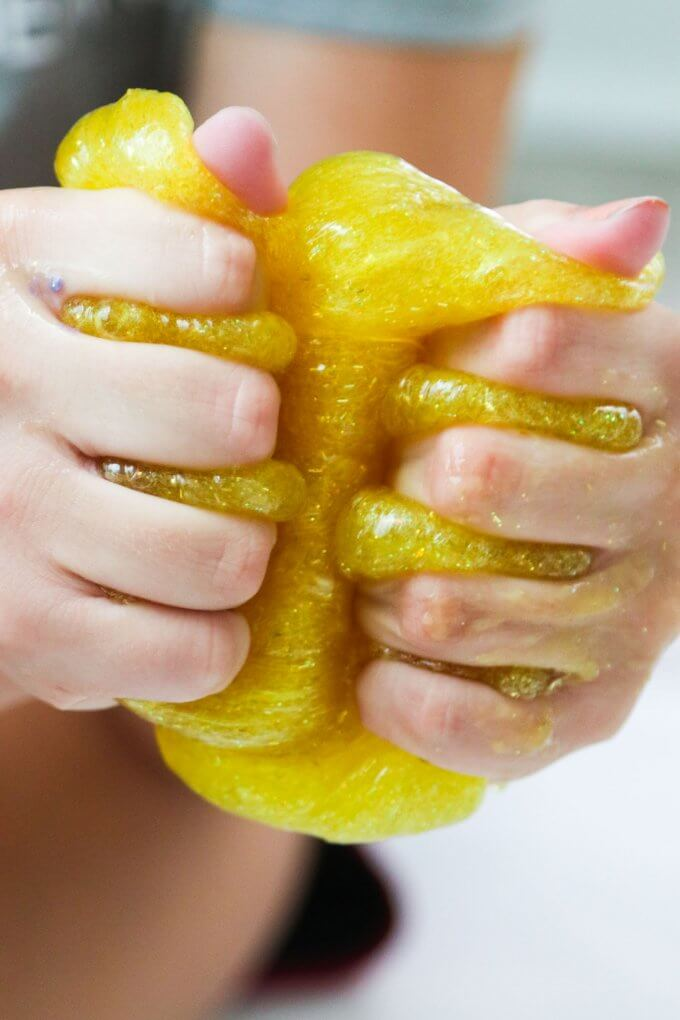 squeezing glitter glue slime in fingers