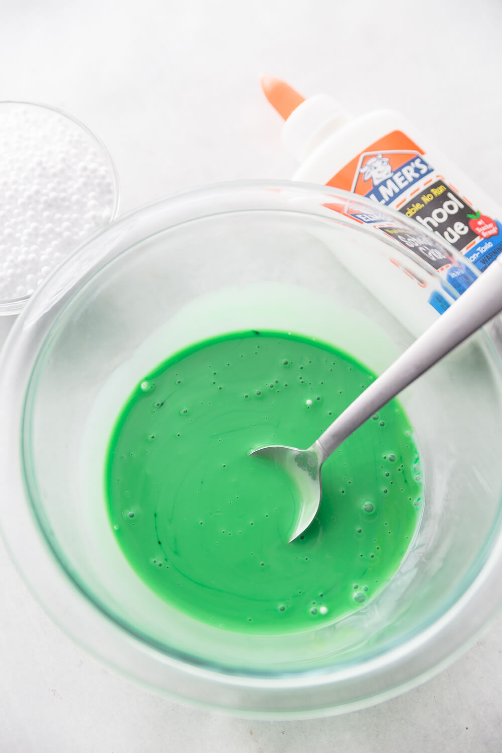 glue, water, and green food coloring in bowl for Halloween floam