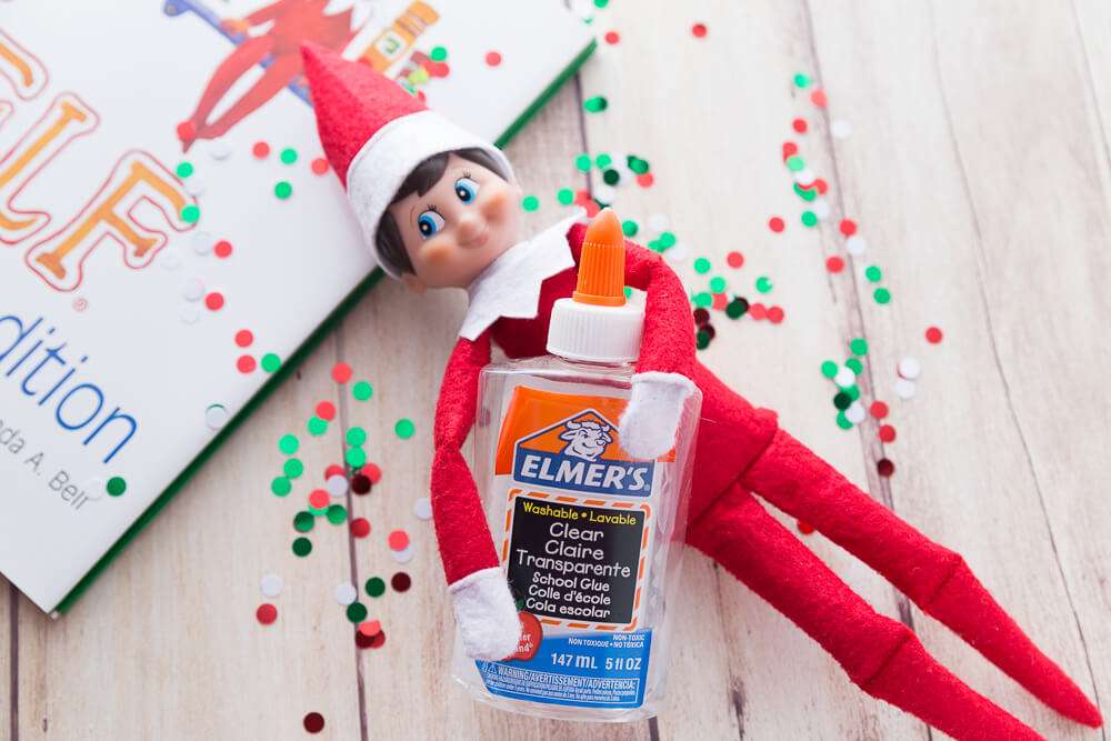 Elf on the shelf holding clear glue for clear slime making