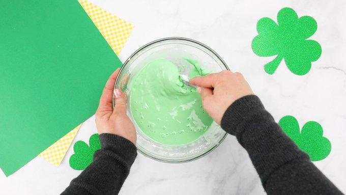 mixing green oobleck in bowl