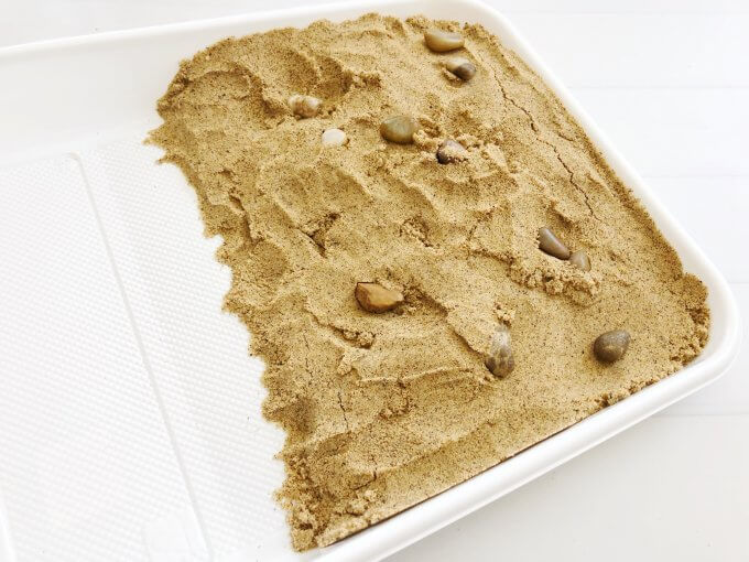 Place sand in half the tray. Make sure it's sloping.