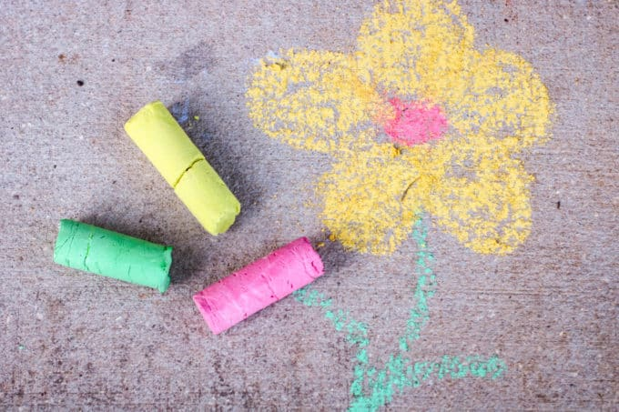 drawing a flower with sidewalk chalk on pavement